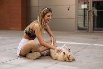 Bonita jovem mulher sorrindo e acariciando cão — Fotografia de Stock