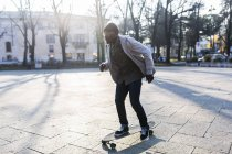 Young man skateboarding on urban square — Stock Photo