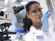 Genetic Research, femme scientifique tenant une feuille avec le code génétique, la composition génétique — Photo de stock