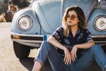 Jeune femme portant des lunettes de soleil, assise à l'extérieur d'une voiture vintage — Photo de stock