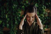 Junge Frau an Wand mit Kletterpflanzen — Stockfoto