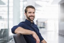Portrait of smiling young businessman sitting in waiting area — Stock Photo