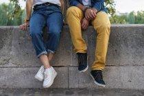 Gambe di una coppia seduta su un muro — Foto stock