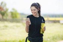 Спортивний жінка, використовуючи смартфон під час охолодження перерва — стокове фото