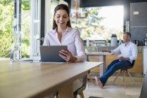 Donna sorridente a casa utilizzando un tablet a tavola con uomo in background — Foto stock