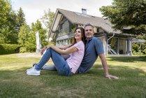 Счастливая пара сидит в саду своего дома — стоковое фото