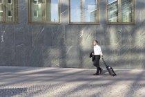 Зрелый бизнесмен гуляет с тележкой в городе — стоковое фото