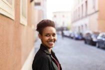 Porträt einer lächelnden jungen Frau, die in der Stadt posiert — Stockfoto