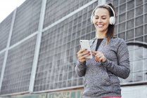 Woman with headphones using smartphone — Stock Photo
