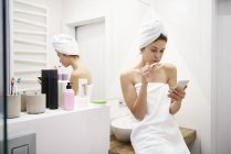 Young woman in bathroom brushing teeth while reading messages on mobile phone — Stock Photo