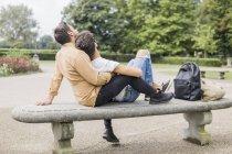 Joven gay pareja relajante juntos en banco en parque - foto de stock