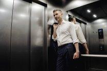Бизнесмен в лифте держит ноутбук — стоковое фото
