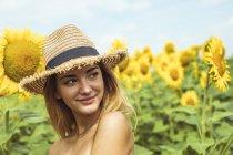 Jovem com chapéu de palha sorrindo em um campo de girassóis — Fotografia de Stock