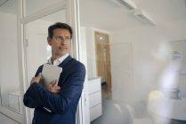 Успішний бізнесмен стояв в офісі з ноутбуком — стокове фото