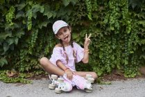 Уверенная маленькая девочка торчит язык сидя на земле с розовыми роликами — стоковое фото