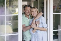Happy mature couple hugging at French window — Stock Photo