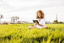 Германия, Кёльн, молодая женщина, сидящая на лугу и использующая цифровые планшеты — стоковое фото