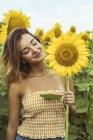 Sorrindo jovem mulher segurando girassol no campo — Fotografia de Stock