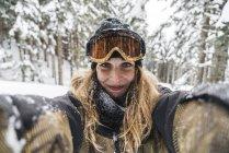 Ritratto di giovane donna sorridente in abbigliamento da sci nella foresta invernale — Foto stock