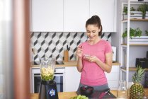 Smiling young woman looking at cell phone in  kitchen, while cooking in blender smoothie — Stock Photo