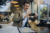 Uomo d'affari maturo seduto in caffetteria, utilizzando smartphone — Foto stock