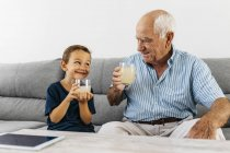 Grandfather and grandson sitting together on couch and drinking lemonade — Stock Photo