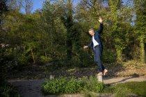Hombre de negocios balanceando descalzo sobre poste en la naturaleza - foto de stock