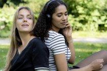 Две девушки в парке слушают музыку — стоковое фото