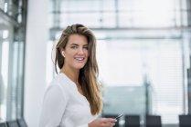 Lächelnde junge Frau mit In-Ohr-Handy — Stockfoto