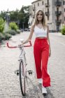 Sorrindo adolescente empurrando bicicleta na cidade — Fotografia de Stock
