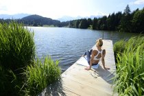 Germany, Mittenwald, back view of woman relaxing on jetty at lake — Stock Photo