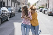 Two girlfriends fooling around on street in city — Stock Photo