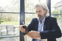 Senior businessman sitting on chair, using smartphone — Stock Photo