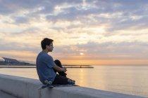 Молода Китайська людина з скейтбордом сидить на стіні на пляжі — стокове фото