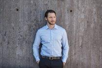 Retrato de homem de negócios em pé na parede de concreto — Fotografia de Stock