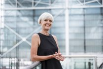 Портрет посміхаючись старша жінка в чорному одязі, спираючись на перила перед скляним фасадом — стокове фото