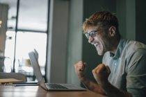 Giovane uomo che utilizza il computer portatile, ridendo con successo — Foto stock