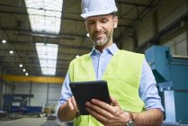 Confident man wearing shirt and safety vest using tablet in factory — Stock Photo
