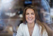 Портрет счастливой молодой женщины за окном — стоковое фото