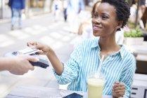 Porträt einer lächelnden Frau, die im Straßencafé mit Kreditkarte bezahlt — Stockfoto