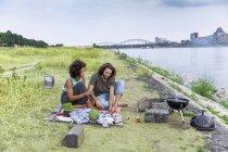 Felice coppia avendo un barbecue a riva del fiume — Foto stock