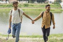 Портрет молодой пары геев с рюкзаками, идущих рука об руку на берегу реки — стоковое фото
