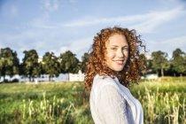 Портрет улыбающейся молодой женщины с вьющимися рыжими волосами, позирующими на природе — стоковое фото