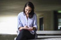 Estudante de sorriso que senta-se no banco ao ar livre tomando notas no caderno — Fotografia de Stock