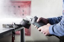 Stonemason working on stone with a grinding machine in his workshop — Stock Photo