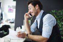 Улыбающийся парикмахер разговаривает в дневнике проверки мобильных телефонов — стоковое фото