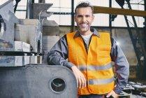 Портрет улыбающегося мужчины в защитной рабочей одежде на фабрике — стоковое фото