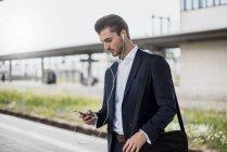 Uomo d'affari alla stazione con auricolari e cellulare — Foto stock