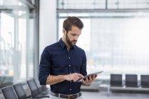 Молодой бизнесмен, стоящий в зале ожидания с помощью планшета — стоковое фото