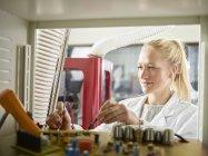 Technicienne entretenant la machine CNC — Photo de stock